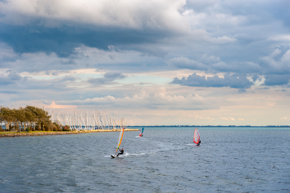 Landscape and windsurfer at the harbor entrance of Orth at the Baltic Sea