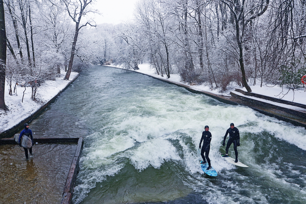 Munich, surfers riding the artificial wave on the Eisbach, small river across the Englischer Garten, in a freezing February morning