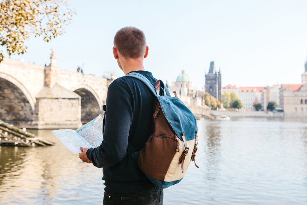 A young tourist man with a backpack standing next to the river Vltava in Prague looks at the map and admires the architecture of the city. Charles Bridge is near. Travel around the Czech Republic.