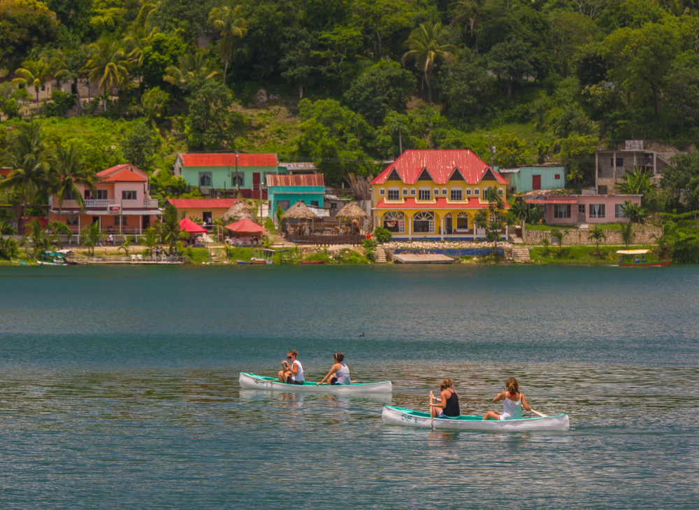 FLORES, GUATEMALA - AUGUST 12, 2008: Women tourists paddle canoes on Lago Peten Itza, near the colonial village of Flores.