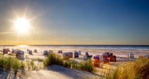 Beach with beach chairs in evening light on the beach of the north sea island Juist in East Frisia, Germany, Europe.