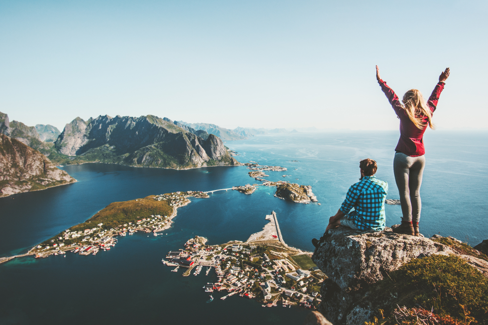 Couple family traveling together on cliff edge in Norway man and woman lifestyle concept summer vacations outdoor aerial view Lofoten islands Reinebringen mountain top