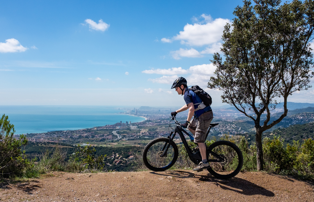 Mountain top view of cyclist on electric bike near Barcelona city Spain