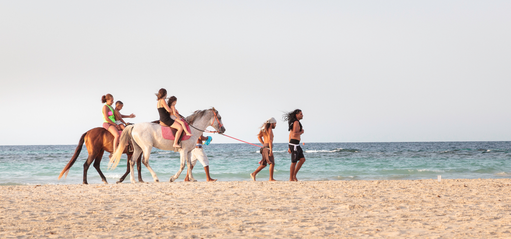 Tourists enjoying a horse back ride on the beach of the island of jerba, south tunisia, 14 august 2017