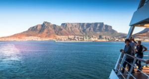 Cape Town, South Africa - April 24, 2017: Unidentified passengers on board a cruise ship watch from deck as the liner leaves Table Bay Harbor with Table Mountain forming a backdrop
