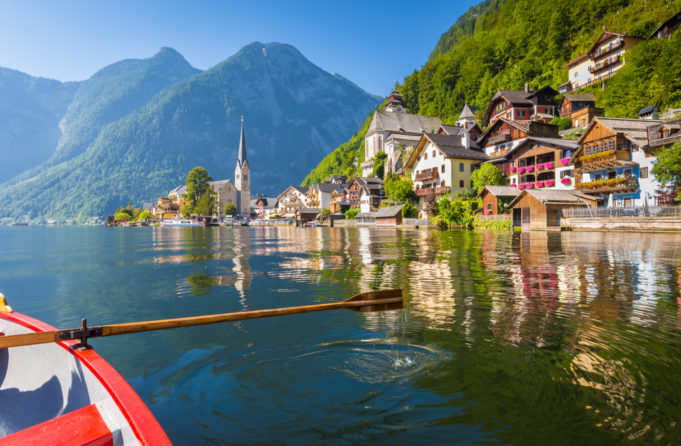 Scenic postcard view of famous Hallstatt lakeside village in the Austrian Alps with traditional wooden rowing boat in beautiful morning light on a sunny day in summer, Salzkammergut region, Austria