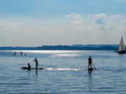 Silhouette of stand up paddle boarders paddling at Lake Chiemsee in Bavaria, Germany