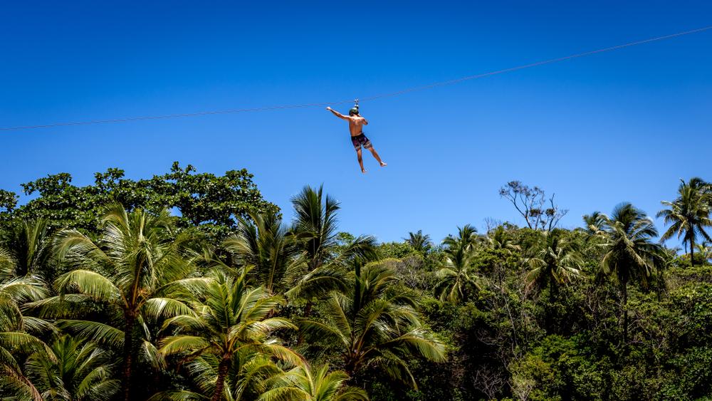 Itacare/Bahia/Brazil - 02-12-2018: Man descends zipline under coconut trees on sunny day
