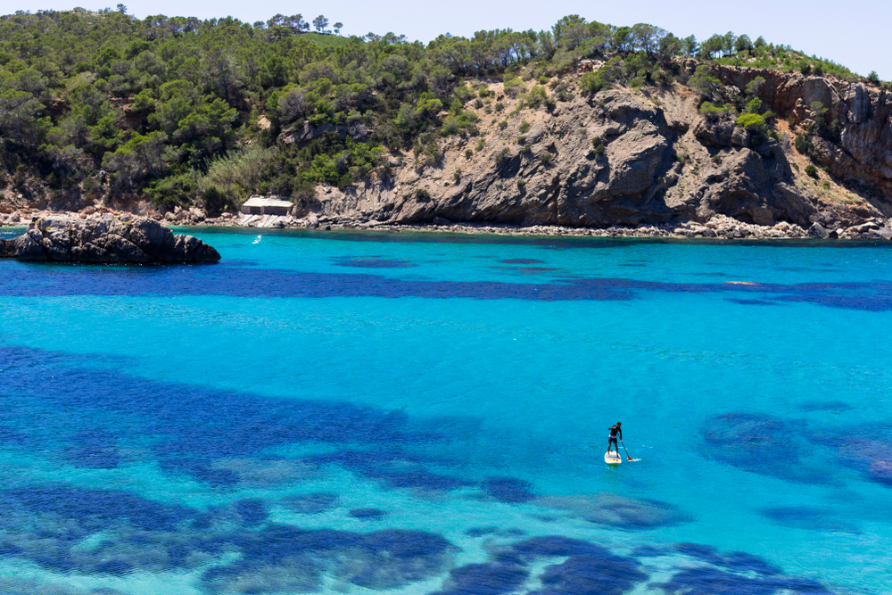 beautiful landscape in Ibiza of blue ocean in a sunny day with a man practicing paddle surf. Summer and holidays concept.