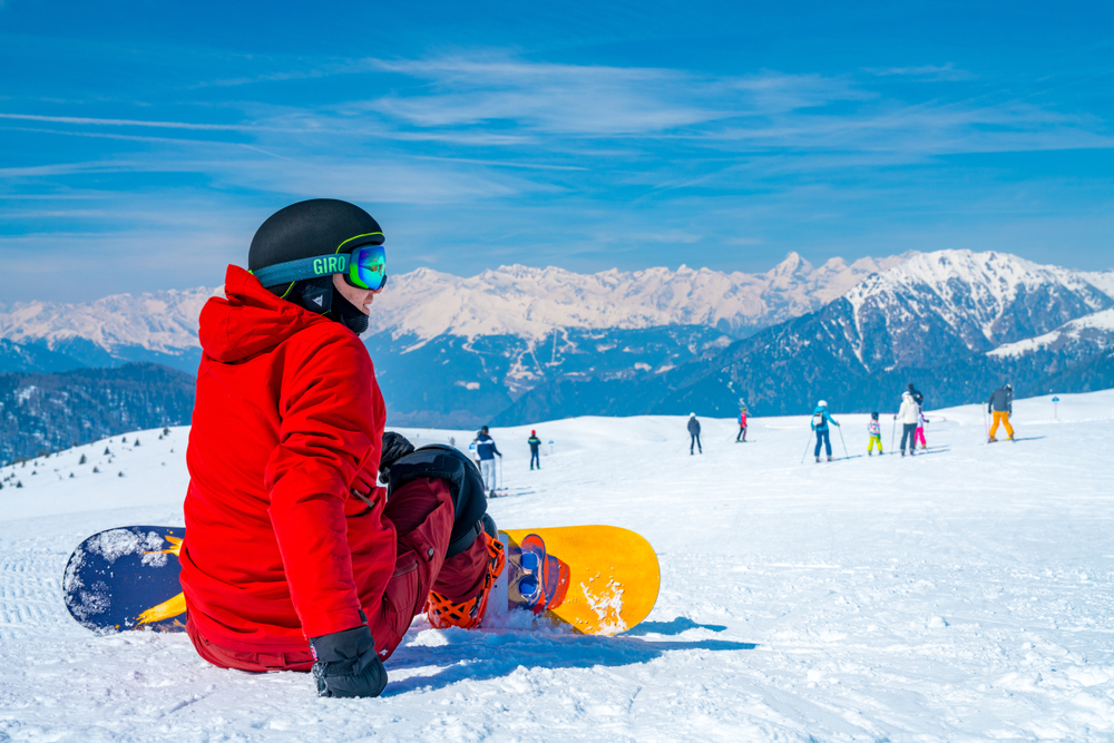Saalbach, Austria. March 20, 2018. young with a snowboard man sitting on the top of the mountain in Alps watching into the horizon. Admiring ski resort. Snowboarding.
