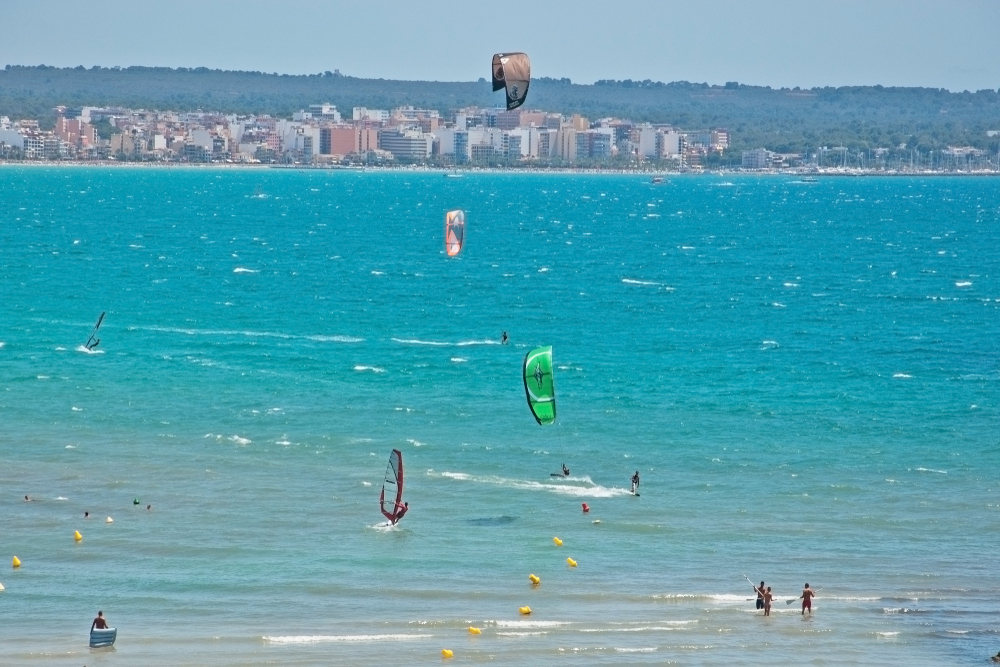 PALMA DE MALLORCA, SPAIN - JULY 20, 2012: Turquoise Playa de Palma filled with kitesurfers on a sunny summer day on July 20, 2012 in Mallorca, Spain.