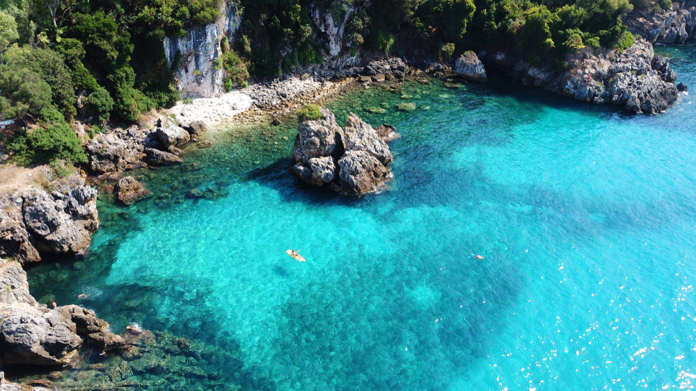 Aerial drone photo of man exerscising canoe in popular mediterranean rocky seascape paradise and turquoise sea
