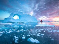 Little red sailboat cruising among floating icebergs in Disko Bay glacier during midnight sun season of polar summer. Ilulissat, Greenland.