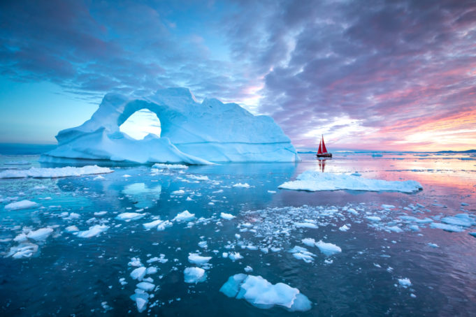 Little red sailboat cruising among floating icebergs in Disko Bay glacier during midnight sun season of polar summer. Ilulissat, Greenland.