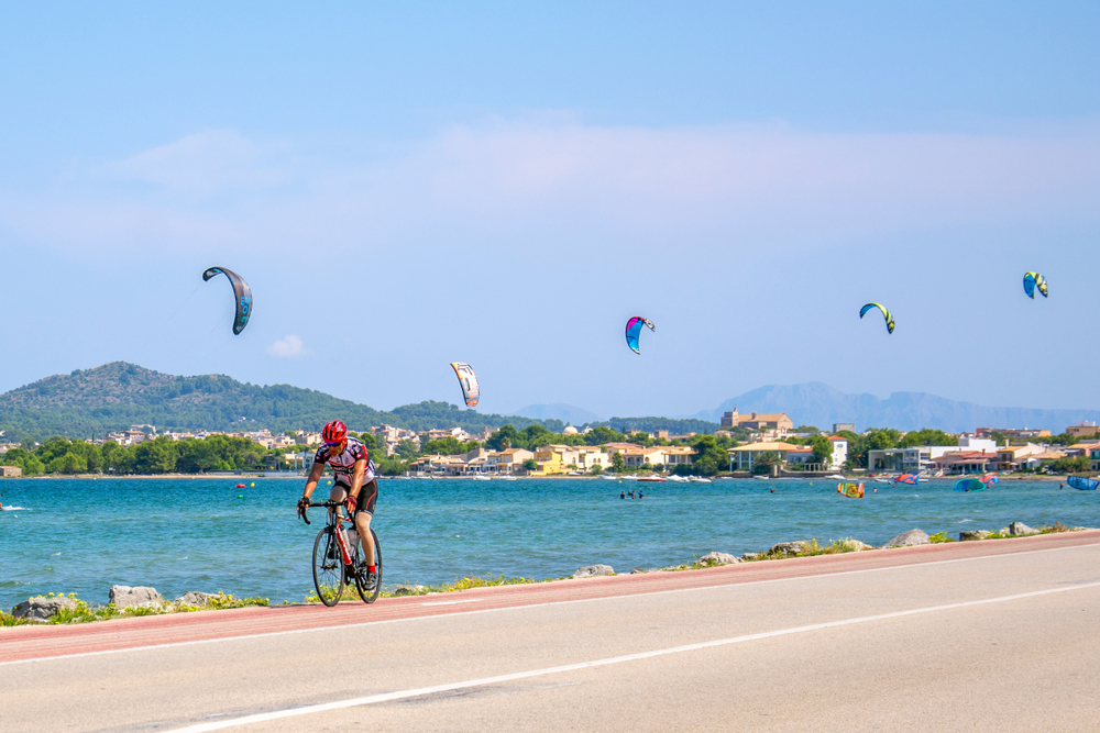 Pollenca, Majorca, Spain - AUGUST 23. 2018: Man riding a bike. Kite Surfing on the beach.