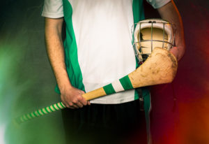 Hurling Player Blank Jersey. Mid section of a hurling player holding a hurling stick and helmet.