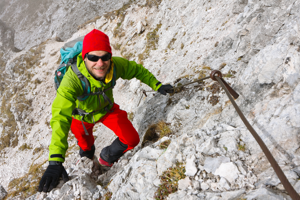 Mountaineer climbing the rocky Kepa mountain wall on a path secured by pins and cables, Slovenia