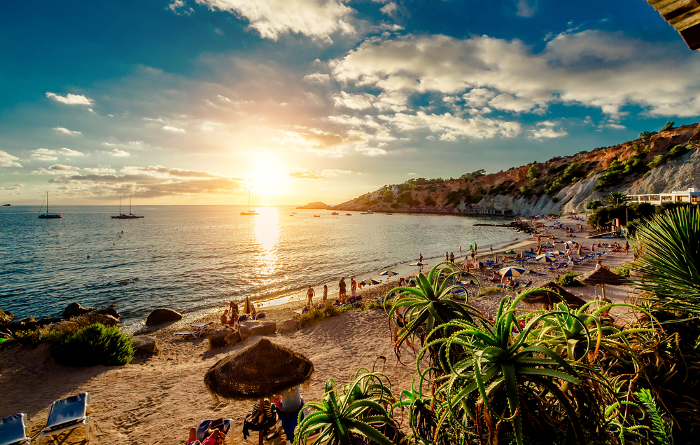 Cala dHort Beach at sunset. People sunbathing, have a party on the sandy tropical picturesque rocky beach during sunset. This beach is very popular for clubbers and vacationers Balearic Islands. Ibiza