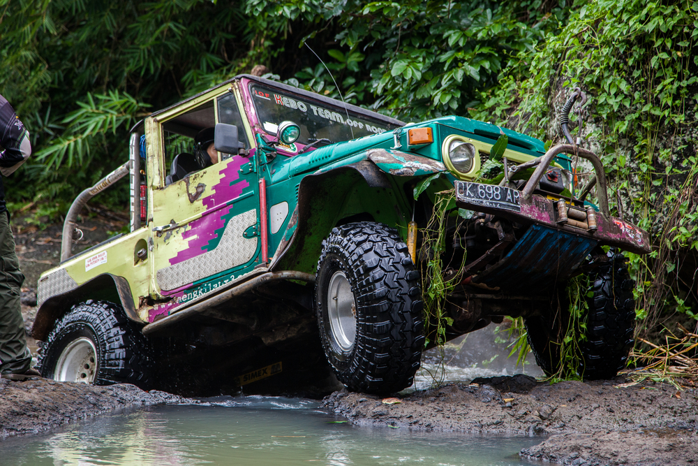 SUV in the tropical jungle - March 7, 2013 Indonesia, Bali. Adventure car enthusiast wading a rocky river using modified four wheel car in the jungle.
