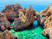 Ponta da Piedade - unique rock formation in the ocean - two boats with tourists visiting famous grottoes. Number one attraction in Lagos, Algrave, Portugal