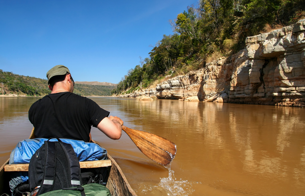 Tourist paddling small canoe on the Tsiribihina river in Madagascar