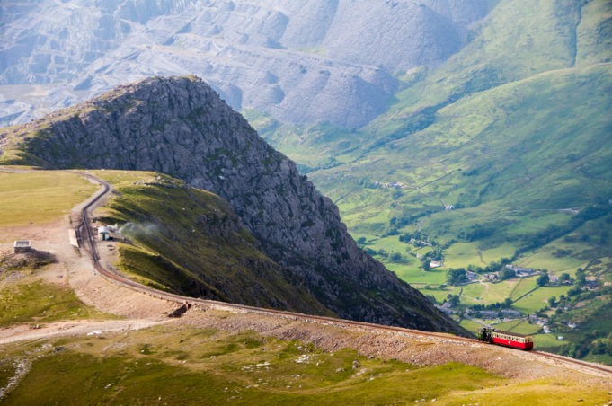A train descends from the summit of Snowdon Mountain on the narrow gauge rack mountain railway with the Llanberis valley and spoil heaps of Dinorwig slate quarry in the distance.