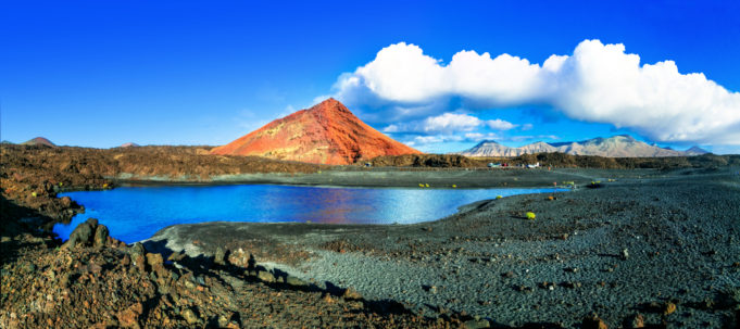 Unique volcanic nature of Lanzarote island with black sands and red mountains