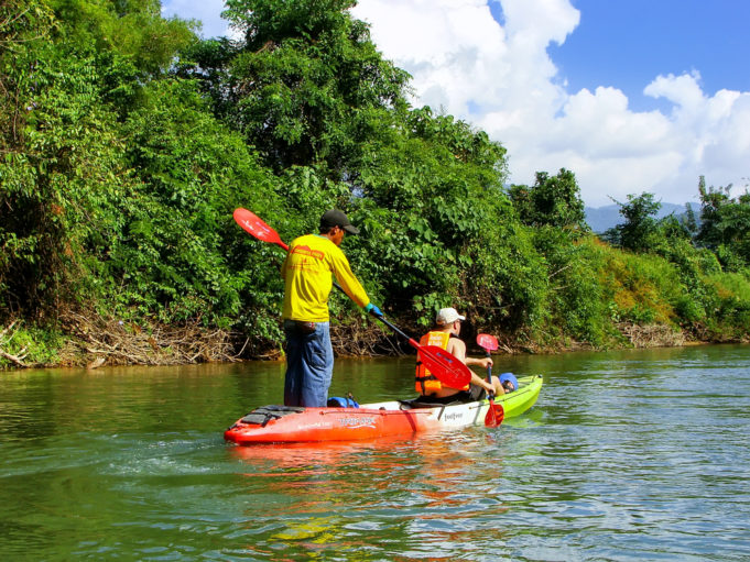 VANG VIENG, LAOS - NOVEMBER 27: Unidentified people go down Nam Song River in kayaks on November 27, 2011 near Vang Vieng, Laos. Kayaking is a popular tourist activity in Vang Vieng.