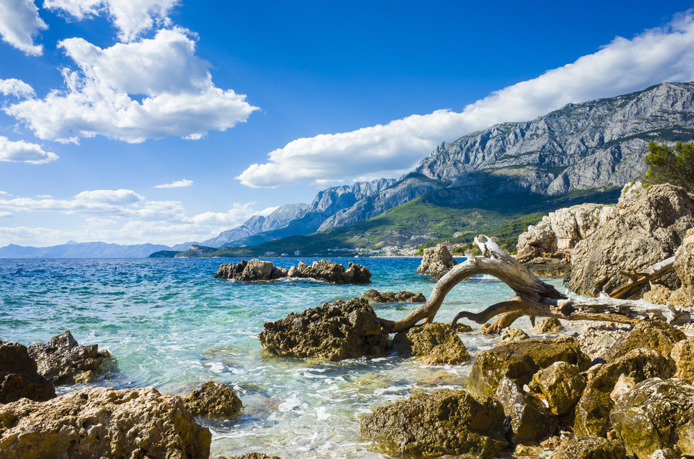 Adriatic Sea Croatia Europe. Beautiful nature and landscape photo. Lovely ocean and nice blue sky with small white clouds. Warm hot summer day. Water, reef, rocks, stones and mountains. Happiness