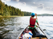 Teenager is paddling in a canoe in the Saimaa lake area / Saimaa, finland, europe