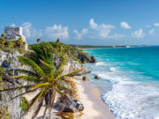 Lizenzfreie Stockfotonummer: 604913387 Ruins of Tulum, Mexico and a palm tree overlooking the Caribbean Sea in the Riviera Maya