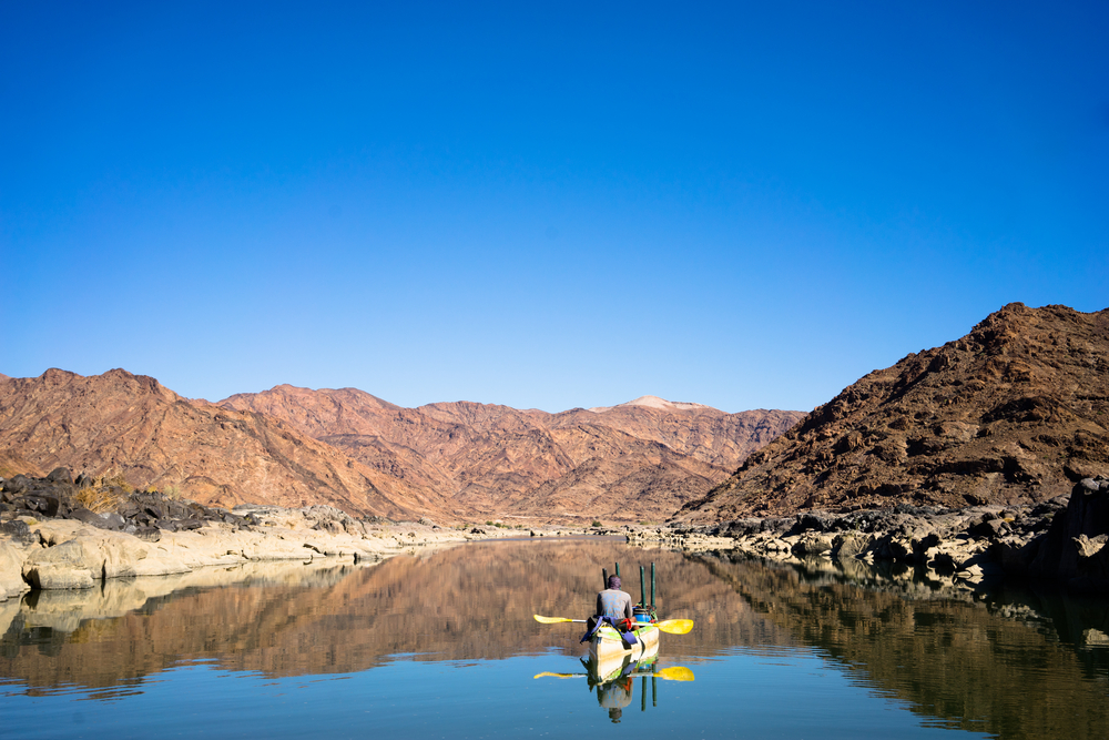 Canoe drifting down the Orange river which forms the border of South Africa and Namibia. Calm water reflecting the barren landscape.