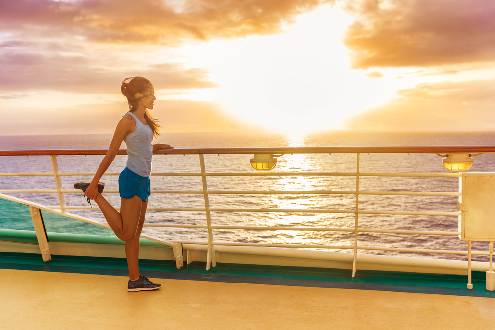 Cruise ship vacation healthy active running lifestyle. Fitness runner woman stretching leg warm-up before exercise on outdoor deck of cruise ship boat. Woman enjoying Caribbean holiday.