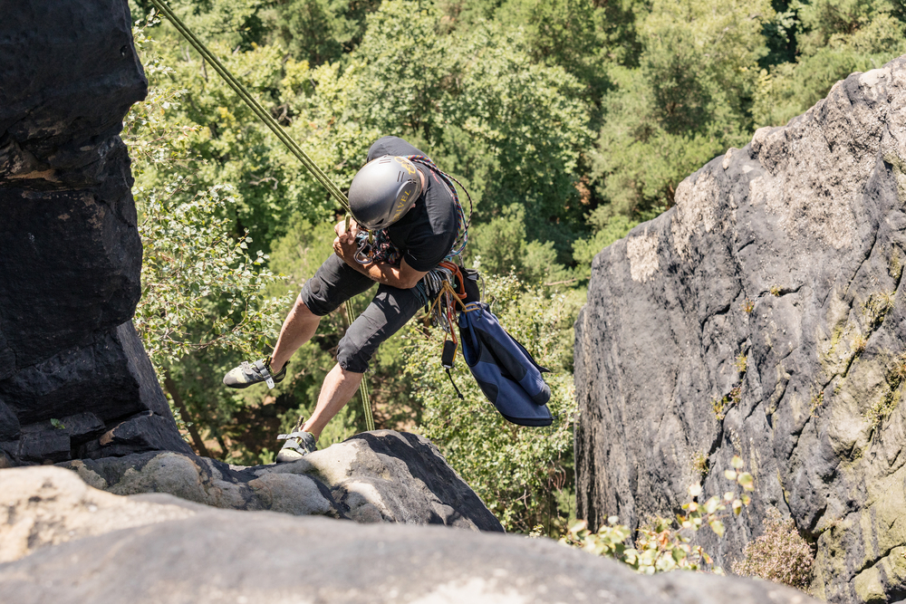 Lilienstein, Germany - August 14, 2017. A rock climber going down a steep mountain with a rope. Climber in Saxon Switzerland (Lilienstein mountain), Koenigstein, Germany.