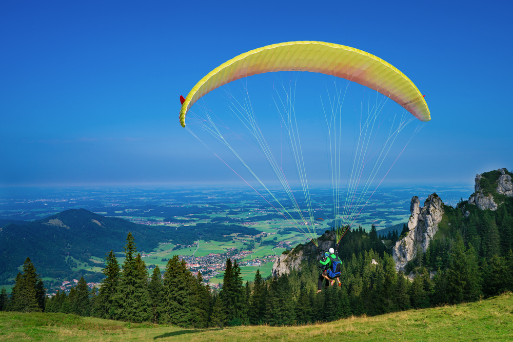 Chiemgau, Germany - September 11. 2016: Tandem paragliders are starting from a slope in the Alpine mountain range near the lake Chiemsee.