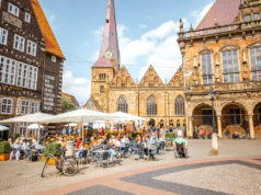 BREMEN, GERMANY - August 09, 2017: View on the Market square with cafes and restaurants full of tourists during the sunny weather in Bremen city, Germany