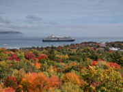 Cloudy morning in Maine overlooking fall foliage and cruise ship departing.