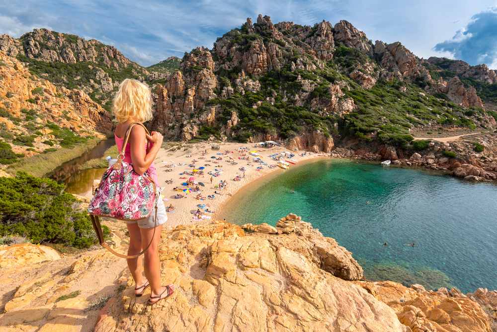Young blonde woman looking at Li Cossi beach (Spiaggia di Li Cossi), Costa Paradiso, Sardinia, Italy