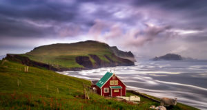 Lonely cabin with sheep on Mykinesholmur island in sunset, Faroe Islands
